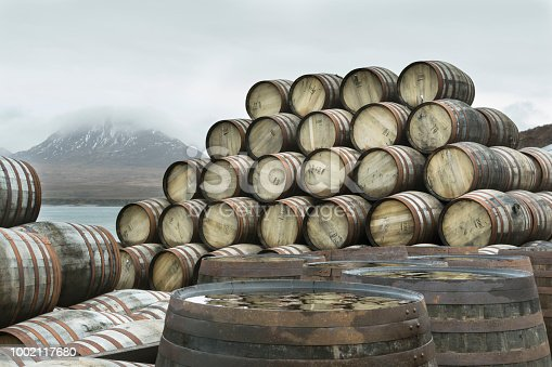 Whisky casks have been stacked up outside Bunnahabhain distillery on the north of the Isle of Islay waiting to be filled with Whisky and transported for storage.