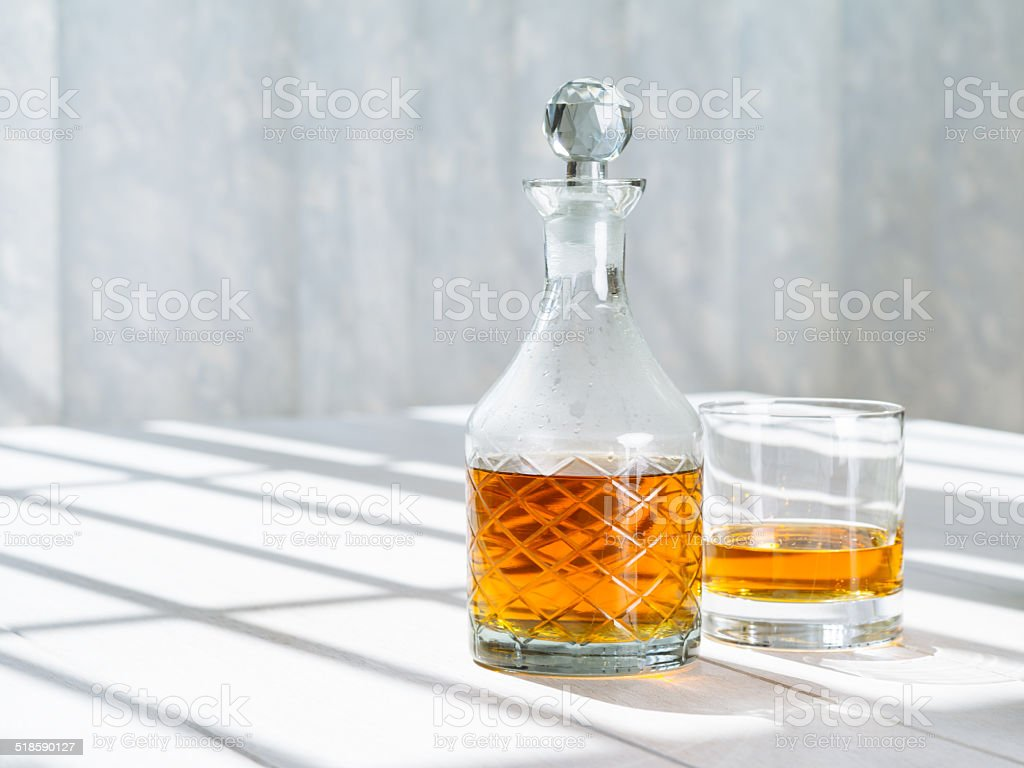 Whisky decanter and rocks glass by the window stock photo