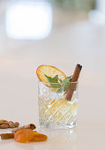Whisky glas mit with mint leaves and cinnamon on the bar.