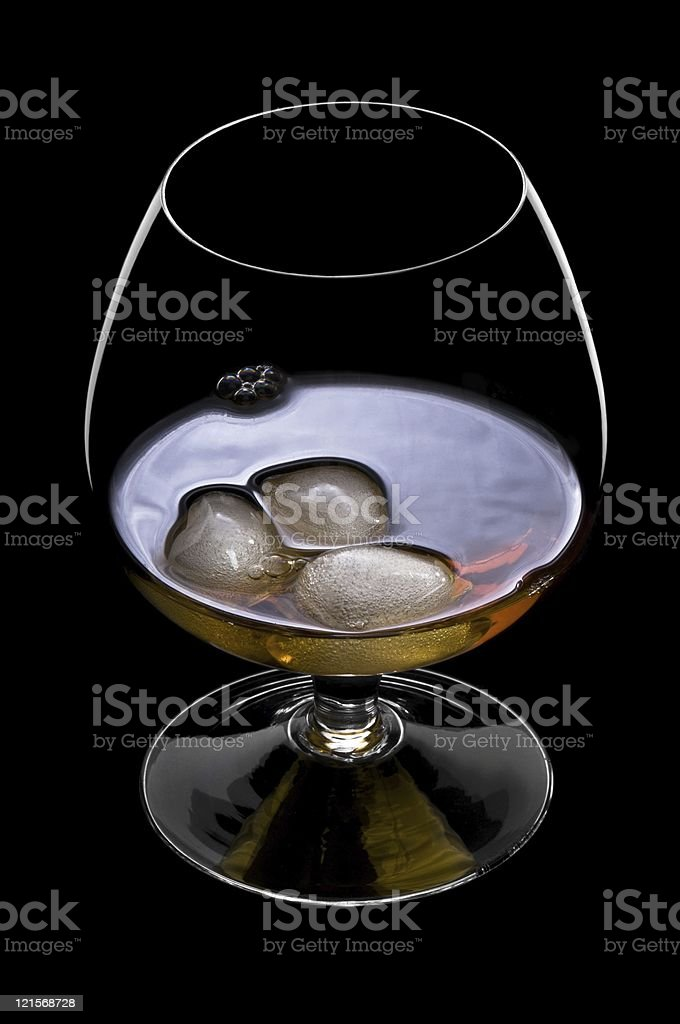 Whisky on the rocks over black in a beautiful glass royalty-free stock photo