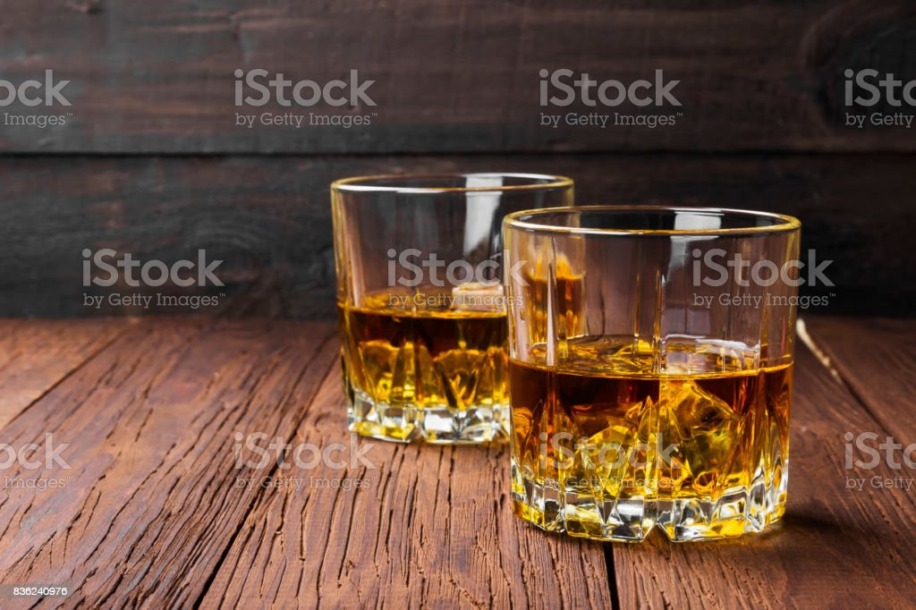 Whisky with ice in two glasses on a wooden background. Copy space. Food background stock photo