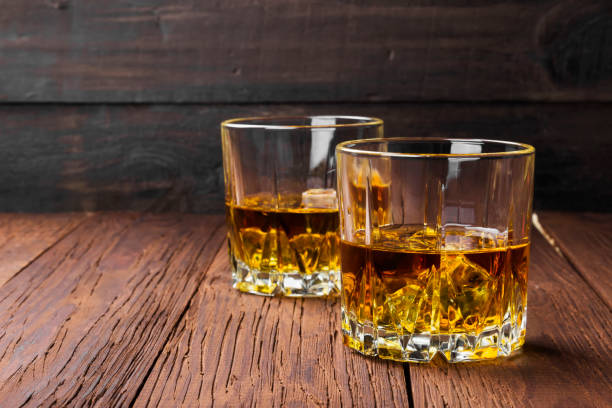 whisky with ice in two glasses on a wooden background. copy space. food background - whiskey stock photos and pictures