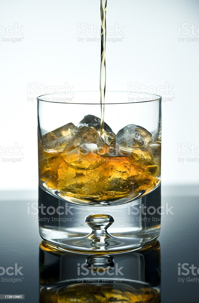 Whisky/Cognac being poured into tumbler royalty-free stock photo