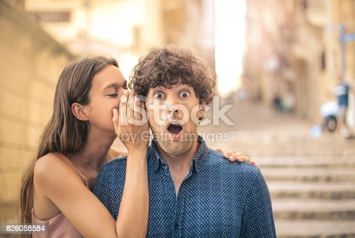 Beautiful young woman whispering a secret into her boyfriend's ear