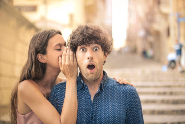 whispering a secret - astonishment stock photos and pictures