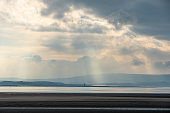Whispy clouds and sunbeams over estuary