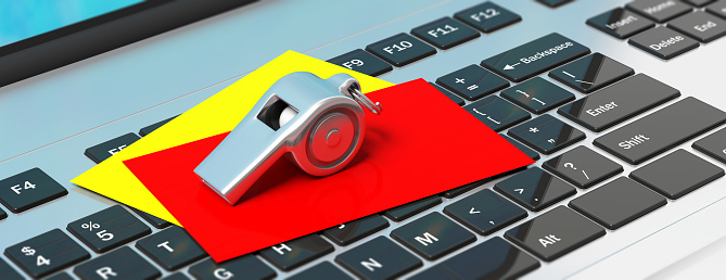 istock Whistle and red yellow cards on computer keyboard, banner. 3d illustration 1056780376