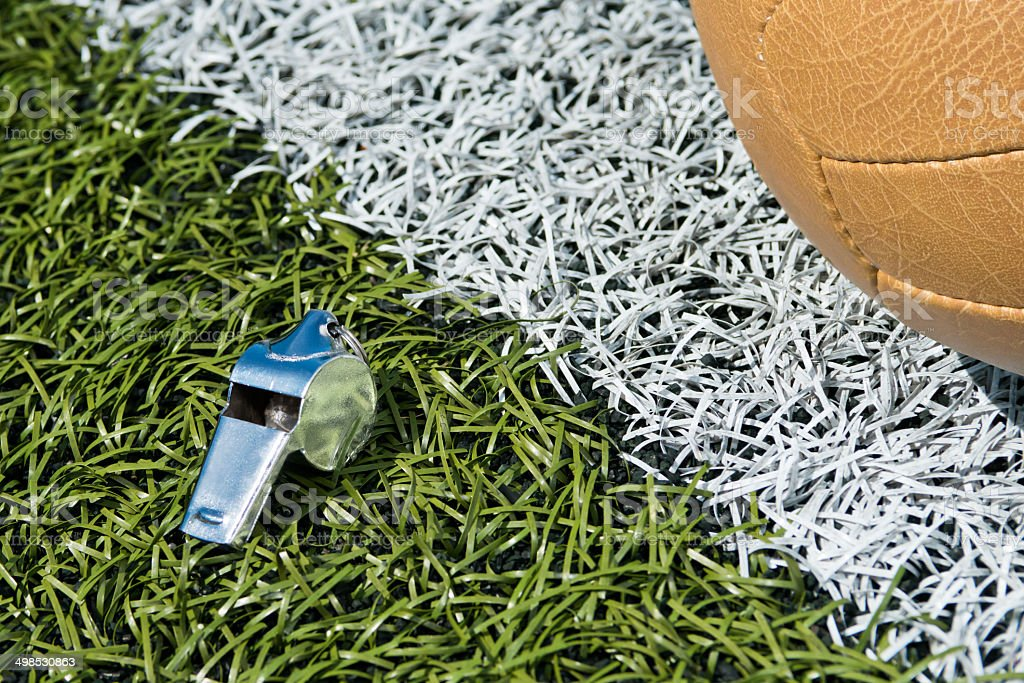 Whistle and soccer ball on a soccer field stock photo