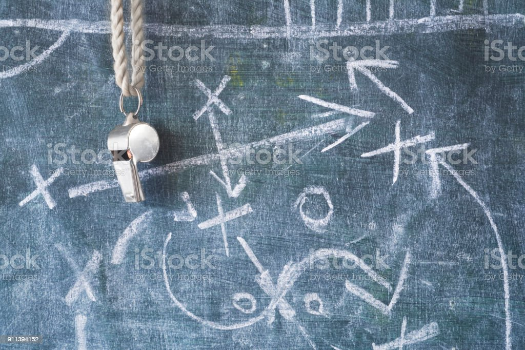 whistle of a soccer or football referee / coach on black board with tactical diagram royalty-free stock photo