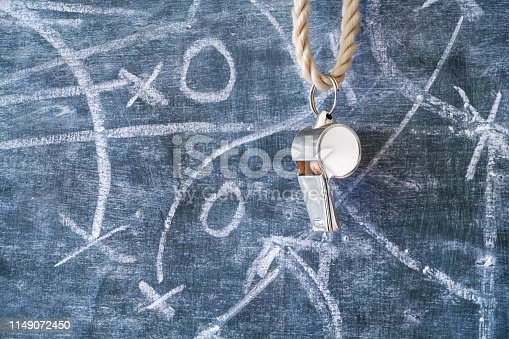 whistle of a soccer or football referee on black board with strategy diagram scribble, free copy space