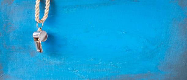 Pfeife eines Fußball- oder Fußballschiedsrichters auf blauem Grunge-Hintergrund, freier Kopierplatz – Foto