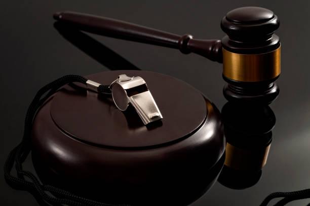 Ley de protección de denunciantes y la idea conceptual de la legislación de libertad de información con silbato de metal y juez de madera en un fondo oscuro - foto de stock