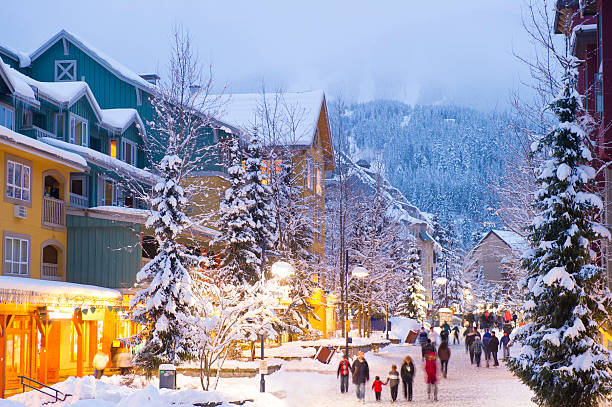 Whistler Village Whistler's world class pedestrian village filled with shops, hotels and restaurants blanketed with fresh snow at dusk ski resort stock pictures, royalty-free photos & images