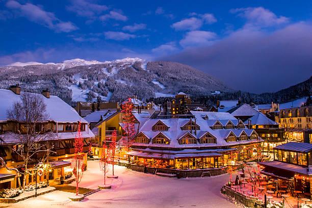 whistler winter village at dusk. - hotel in den bergen stock-fotos und bilder