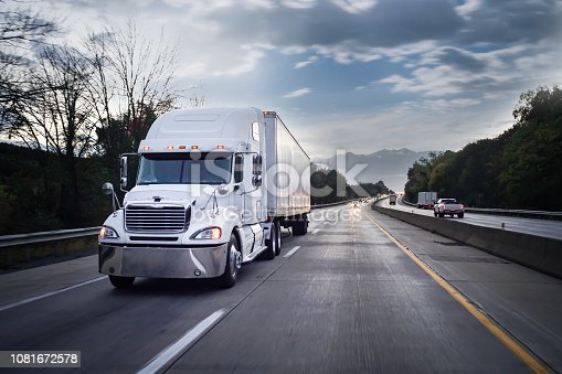 Big 18 wheeler semi-truck delivering freight on the highway in the evening hours