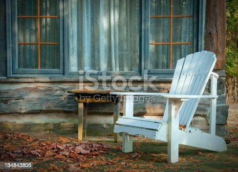 A white adirondack chair on a wooden deck.