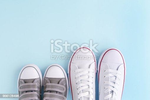 White adult and kids sneakers on blue background, top view