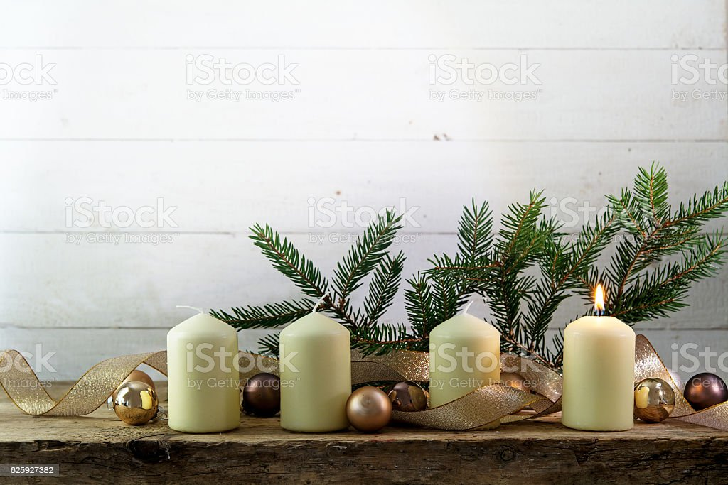 white advent candles, one burning, bright wooden background stock photo