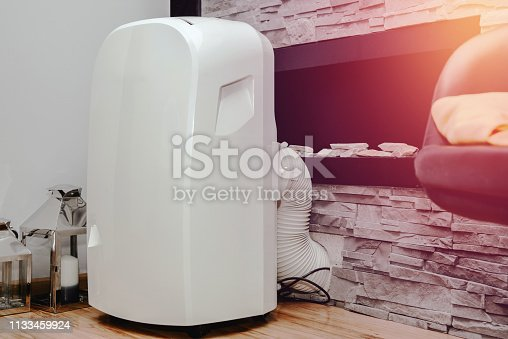 istock White air conditioner in the apartment. The concept of cooling and cleaning the air at home. 1133459924