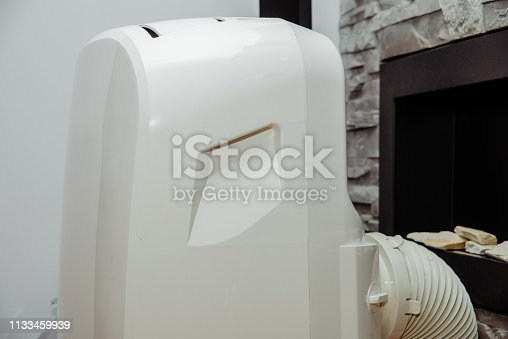 istock White air conditioner in the apartment. The concept of cooling and cleaning the air at home. 1133459939