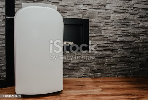 istock White air conditioner in the apartment. The concept of cooling and cleaning the air at home. 1133459978