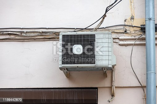 947099530 istock photo White air conditioning on the old wall of the house with the old wires of communication on the plastic drain pipe above the window. Cooling and comfort at home in the hot season. 1159442870