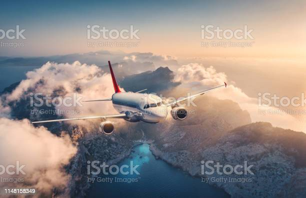 Photo of White airplane is flying over mountains and low clouds at sunset in summer. Landscape with beautiful passenger airplane, sky in clouds, sea, sunlight. Travel. Commercial plane. Aerial view of aircraft