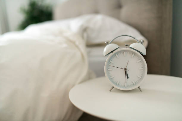 white alarm clock and bed at home stock photo