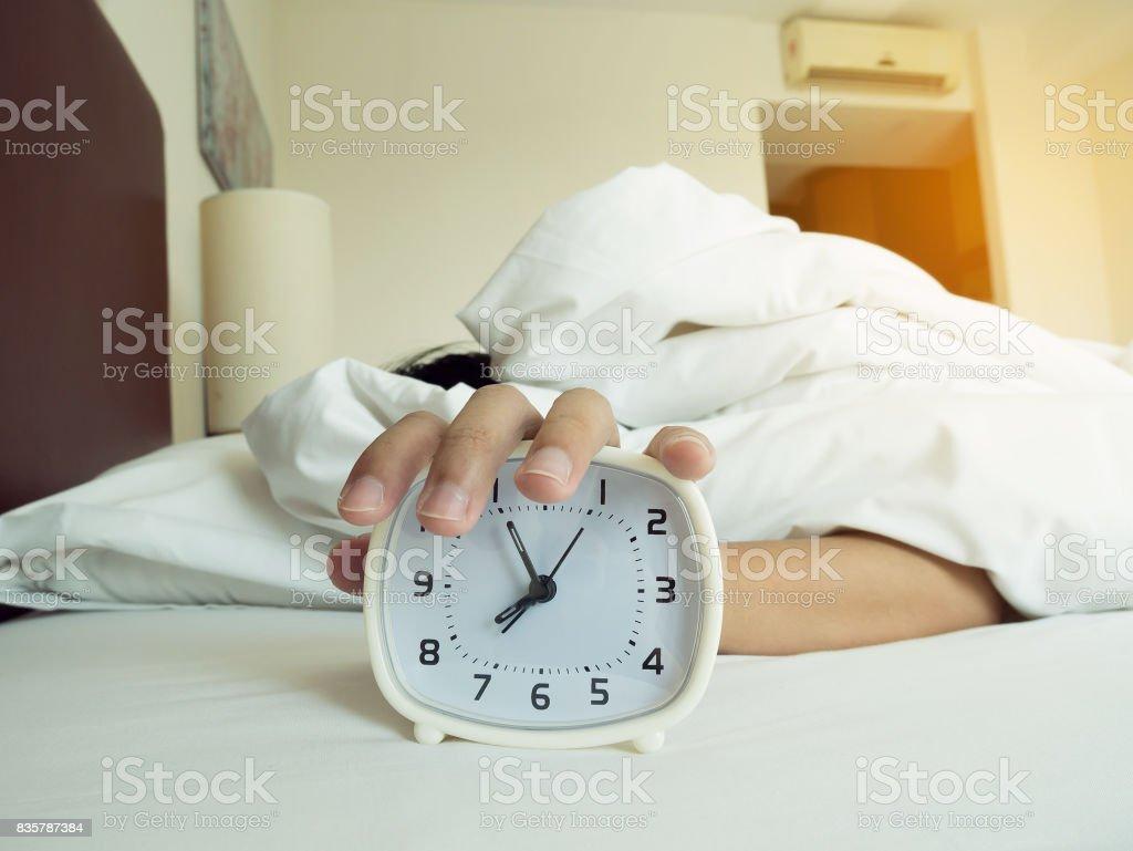 despertador branco e homem adormecido - foto de acervo