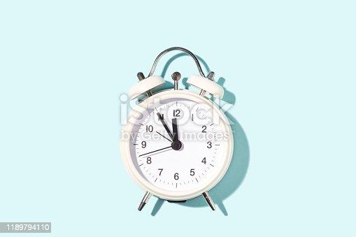 1139289535 istock photo White alarm clock on blue background. 1189794110
