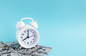 istock White alarm clock on dollar bills on a blue background. Time is money. The concept of business planning and Finance 1255147351