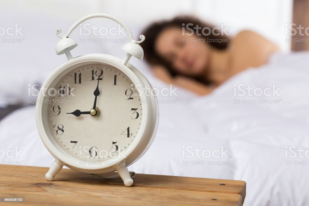 White alarm clock on the background of a sleeping girl. stock photo