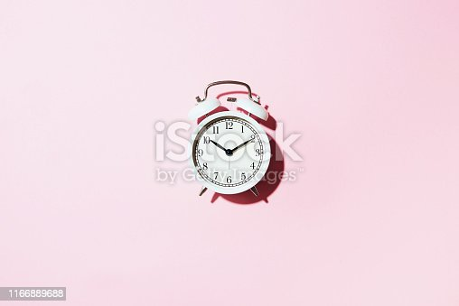 istock White alarm clock with hard shadow on pink background. Top view. Wake up alert concept. Morning routine. 1166889688