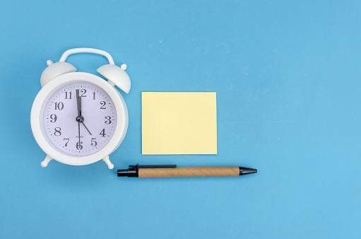 istock White alarm clock with yellow record sheet, pen on blue background, copy space 1256733004