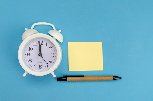 istock White alarm clock with yellow record sheet, pen on blue background, copy space 1257165213