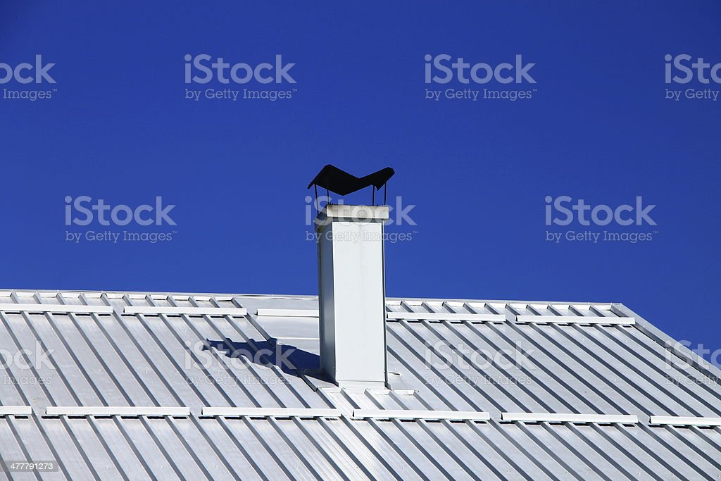 White aluminum roof with chimney and blue sky stock photo