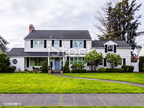 Photo of a white American colonial style home exterior on a bright overcast spring day