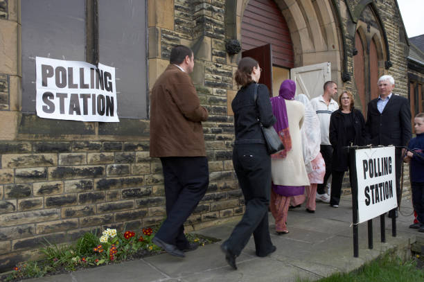 white and asian voters entering polling station in dewsbury - polling place stock pictures, royalty-free photos & images