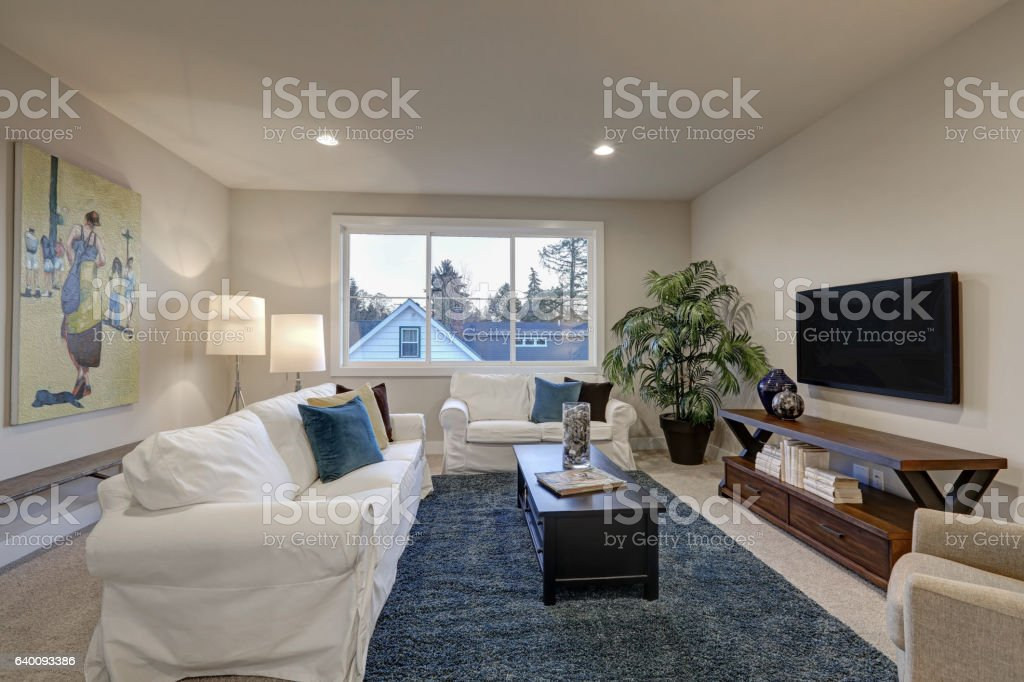 white and beige living room interior with blue accent rug stock