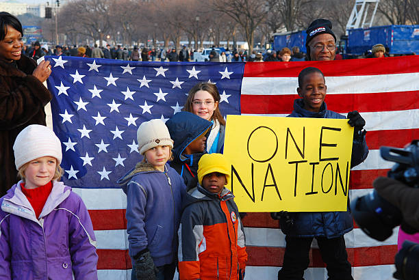 "One nation White and black children stand with the American flag and a sign that reads ""one nation"" on the eve of the inauguration of Barack Obama in January 2009. inauguration stock pictures, royalty-free photos & images"