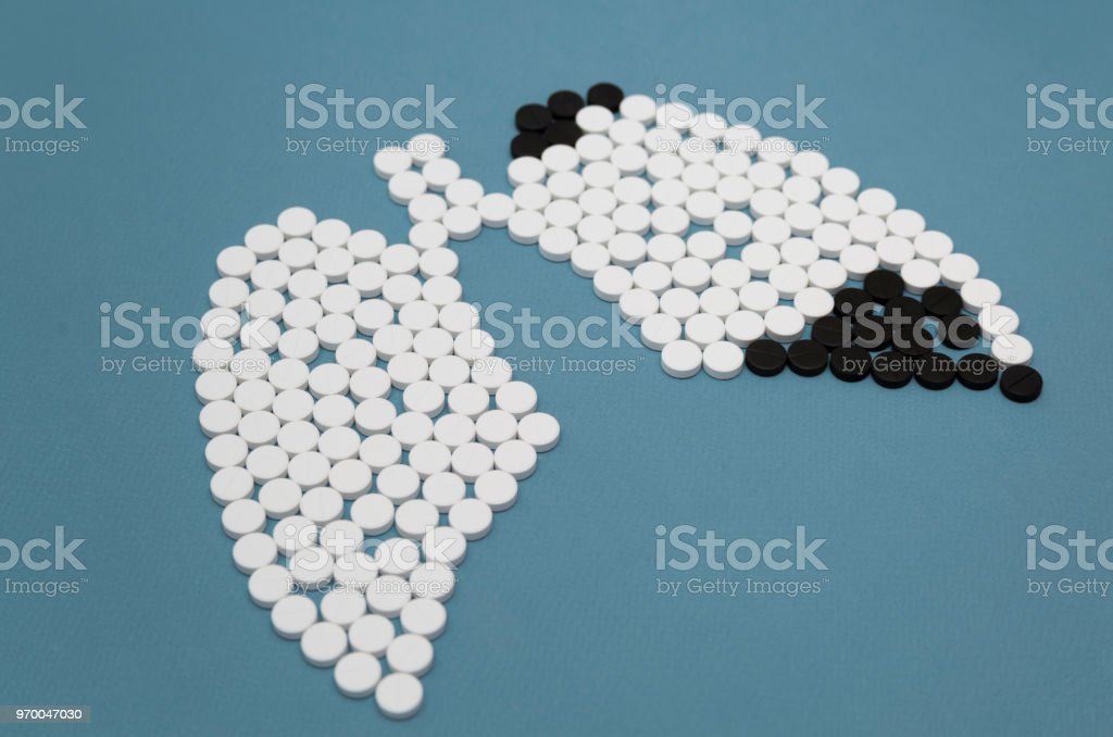White and black pills in the shape of healthy lungs and disease lungs stock photo