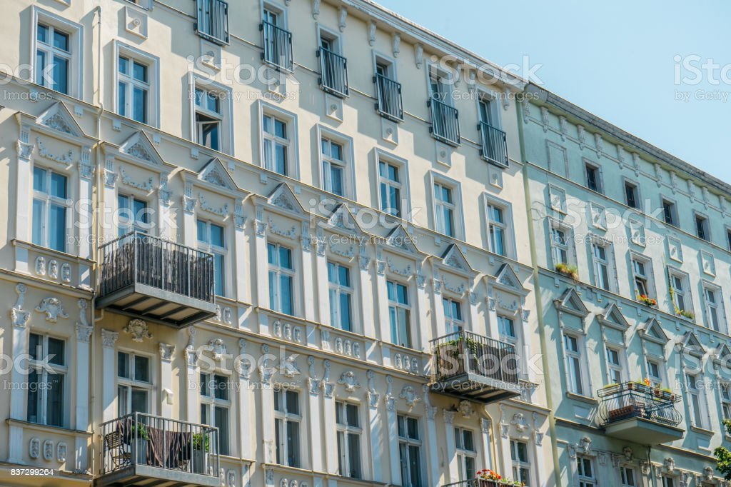 white and blue apartment facades in a row stock photo