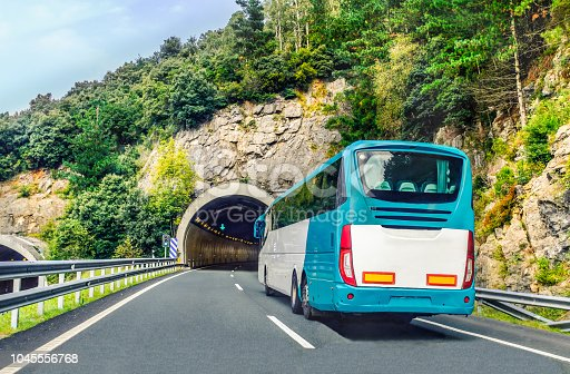 A white and blue coach, or long haul bus for tourists drives through the mountain tunnels and roads of Northern Spain, Europe on a summer day.