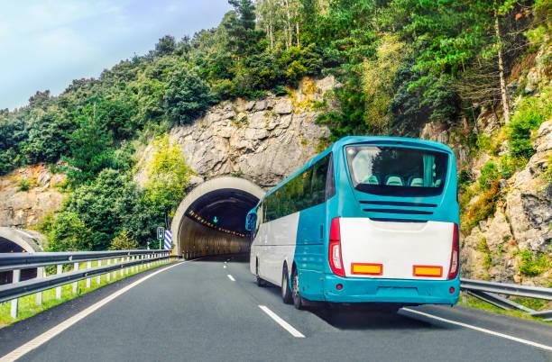 Einen weißen und blauen Coach oder Langstrecken-Bus für Touristen fährt durch den Berg Tunnel und Straßen im Norden Spaniens, Europas an einem Sommertag. – Foto
