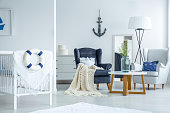 Decorative white and blue lifebuoy hanging on baby's crib in bright room