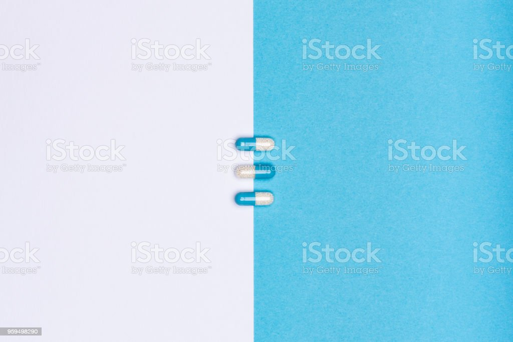 White and blue pills isolated on bicolor white and blue colored background. Medication and prescription pills minimal flat lay with copy space. stock photo