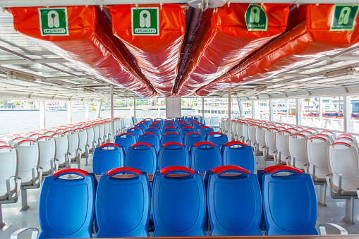 White and blue seats and life jackets or bench rows, a gray floor on a ferry boat deck as a background or a pattern in istanbul