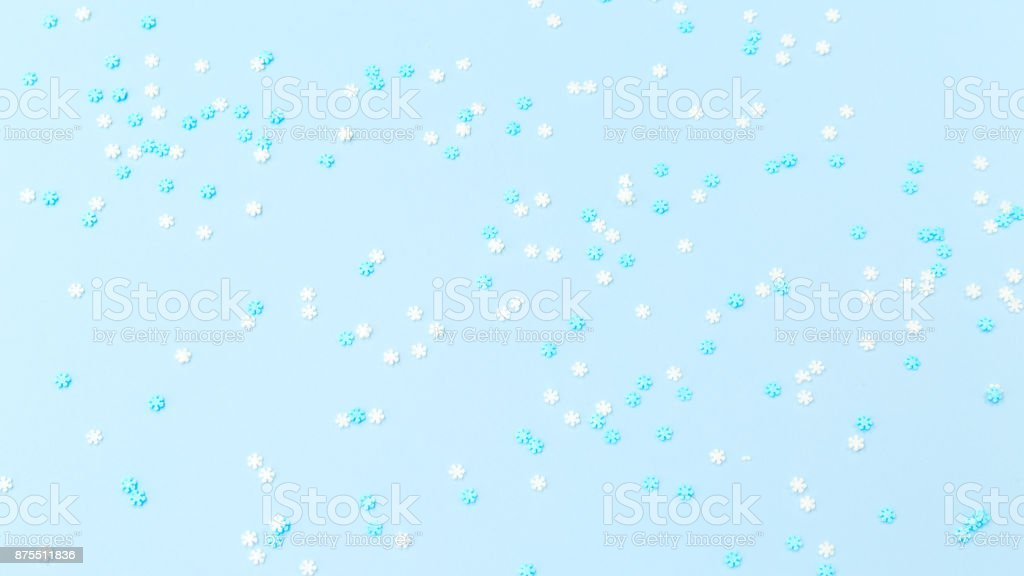 White and blue snowflakes sprinkles on blue. Festive holiday background. Celebration concept stock photo