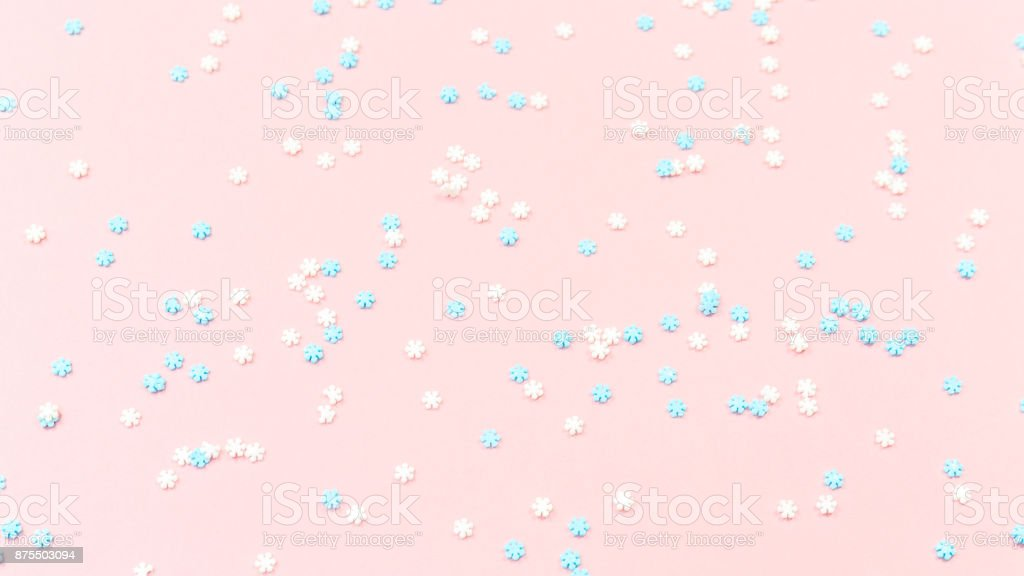 White and blue snowflakes sprinkles on pink. Festive holiday background. Celebration concept stock photo