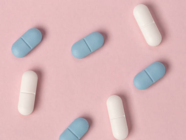 White and blue tablets on a pink background. View from above stock photo